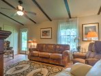 The living room has a comfortable leather couch and plush armchairs.