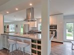 The fully equipped modern kitchen boasts stainless steel appliances and a center island with a stovetop, stainless...