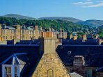 View over the rooftops of Edinburgh and the pentland hills from the living room