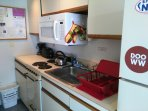 Full Galley Kitchen. Microwave, 4 burner stove, coffee maker, toaster, pots, pans, dishes, utensils