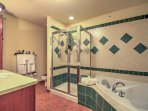 The master bath boasts tasteful tile walls and flooring, a large bathtub, and a walk-in shower.