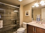 The main floor bathroom has a single sink, large vanity mirror, and shower.