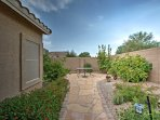 The fenced outdoor space is complete with a wonderful stone walkway and lush greenery.