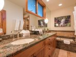The master bathroom features a double vanity and separate tub and shower.
