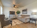 The living area has a flat-screen TV and comfortable couches.