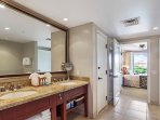 Master bath features a double vanity, a glass walk-in shower, and a separate soaking tub