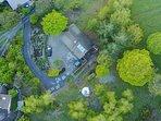 Notre maison vue du drone d'un locataire: chemin d'accès, nombreuses places de parking,bois alentour