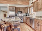 Gourmet display kitchen with Viking refrigerator, 5-burner gas stove, granite counters, and island with 4-bar seats