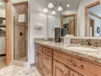 Master bathroom with dual vanities, stone shower and large walk-in closet with built-in dresser