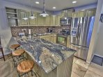 View of the kitchen with new stainless steel appliances, granite counters, docking station, Kurig, and 3-bar seats