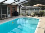 Enclosed Heated Pool with Sitting and Dining Table and Grill