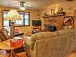 The tastefully decorated living room offers plush furniture, a flat-screen cable TV,  and a wood-burning fireplace.