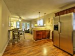 The kitchen is complete with natural wood elements, stainless steal appliances, and sleek hardwood floors.