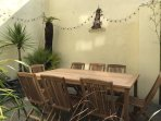 Mediterranean style patio garden with teak table and chairs seating 8