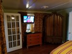 Other side of master bedroom with TV and armoir