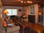 Den sofa on opposite wall of both guest bedrooms with wood burning kiva fireplace