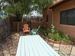 Coyote fenced back yard with table, chairs, propane grill, fire pit sweeping mountain / pasture views