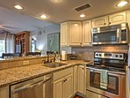 The fully equipped kitchen features granite counters, tile back splash, and stainless steel appliances.