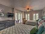 The second bedroom features 2 queen beds and a sliding door that opens up onto the patio.