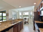 Open kitchen with stainless steel appliances and granite counters.