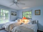 Large windows offer an abundance of natural light in the bedroom.
