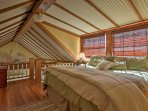 Wood beams and a vaulted ceiling highlight the loft area, which features a king-sized bed.
