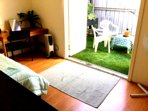 Bedroom 2.  French doors opens out to private backyard garden with garden chairs and hammock