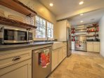 The fully equipped kitchen has stainless steel appliances and a farmhouse sink.