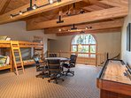 Upper level loft recreation area with card table, shuffle board and two twin bunks.
