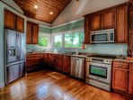 Beautiful open kitchen with hard wood floors, granite counter tops and translucent glass subway tiles