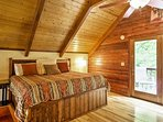 The bedroom upstairs in the open loft features a king bed and access to the balcony.
