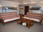 Lower level sitting area/bunk area with two twin bunk beds and futons