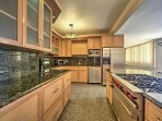 The fully equipped kitchen boasts full-slab granite counters, wood elements, and stainless steel appliances.