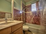 This bathroom boasts a spacious shower/tub combo.