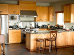 kitchen features an 8 burner wood stove, custom cabinets and stone  counter tops from Brazil