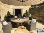 Sunny courtyard and stone BBQ to use at the rear of the property .