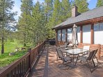 Outdoor deck space with patio furniture and a grill overlooking a small creek