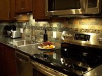 Kitchen is fully-equipped with small appliances, cookware, dishes.