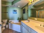 The master bathroom has dual sinks, a large vanity mirror, jetted tub, and a stand-up shower.