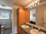 This en-suite  bathroom offers a tub-shower combo and double sinks.