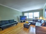 The living area features leather couches surrounding a large TV with hundreds of Satellite channels.