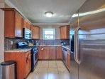 The fully equipped kitchen features granite countertops, tiled backsplash, and stainless steel appliances.