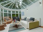 The beautiful conservatory with lovely views over the landscaped garden and into Johnston Gardens