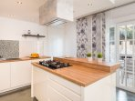 Fully equipped kitchen with exit to terrace with outdoor dining area and BBQ