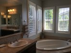 Master bath with two vanities and a soaking tub