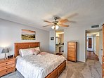 The master bedroom has a comfortable queen bed with a beautiful wooden frame and night stand.