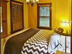 The master bedroom boasts a plush queen bed.