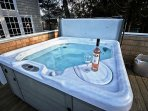 Large upper deck with a hot tub, patio table for 6 and a gas BBQ