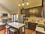 The home's kitchen boasts sleek dark wood elements, a 2- person breakfast bar, and stainless steal appliances.