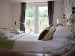 Light and bright bedroom with french doors onto the garden